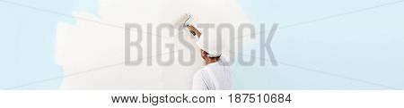 Rear view of painter man painting the wall with paint roller isolated on big empty space web banner