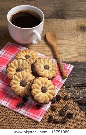 Cookies with chocolate and cup of hot coffee on old wooden table