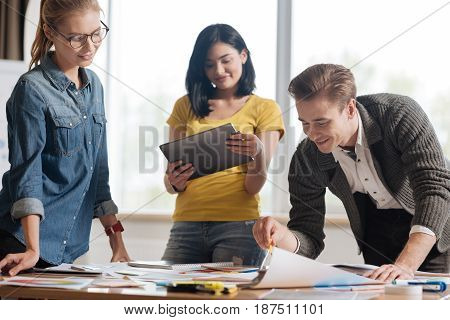 Modern device. Nice beautiful delighted woman holding a tablet and looking at its screen while standing around the table with her colleagues