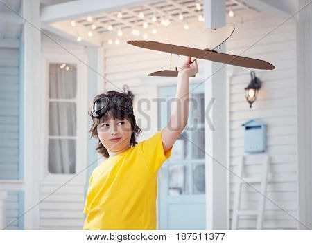 happy boy play with paper airplane in hand, child dreams about traveling by aeroplane