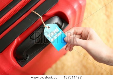Female hand with with label on red suitcase, closeup. TRAVEL INSURANCE concept