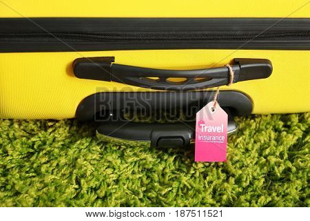 Yellow suitcase with label, closeup. TRAVEL INSURANCE concept