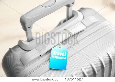 Grey suitcase with label, closeup. TRAVEL INSURANCE concept