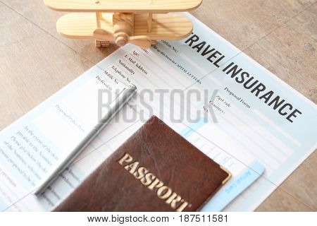 Passport with arrival cards and pen on travel insurance form