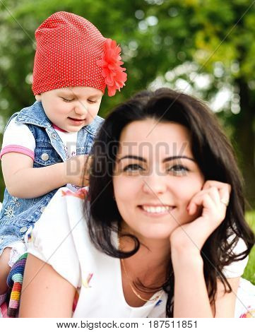 Mom and little daughter in the park focus on the baby