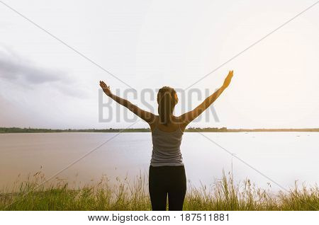 woman with open arms at river and sunshine