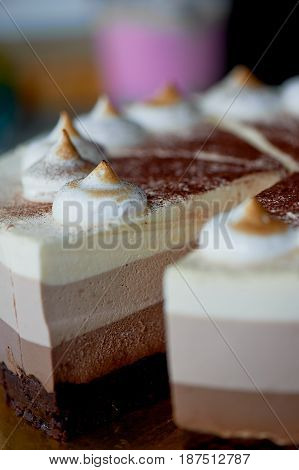 four layer cake with shades of brown. Here cream to chocolate.