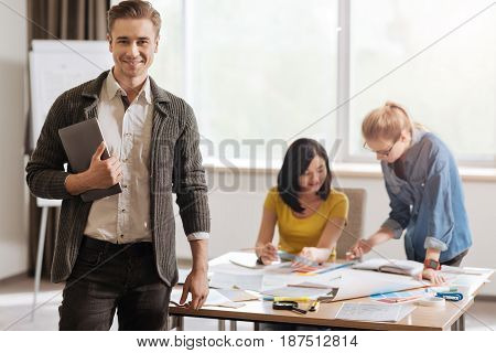 Modern designer. Handsome happy young man holding a tablet and looking at you while being ready to work
