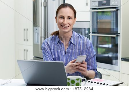 Portrait Of Female Freelance Worker Using Laptop In Kitchen At Home