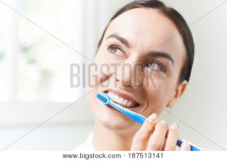 Woman Brushing Teeth With Toothbrush In Bathroom