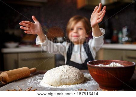 Cute little girl claping hands with flour of a dough in the kitchen. Horizontal indoors shot.