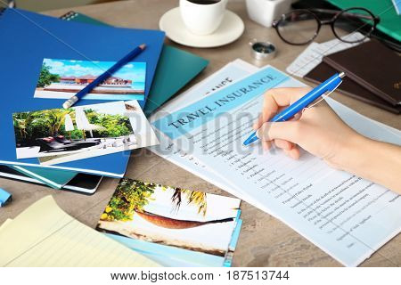 Woman filling in blank travel insurance form on table