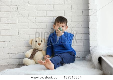 Little boy using nebulizer while sitting on floor near window. Allergy concept