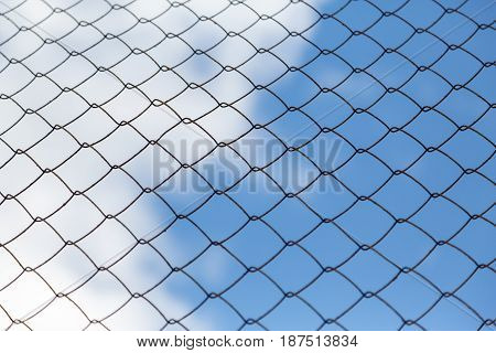 Metal mesh netting on the blue sky background and clouds