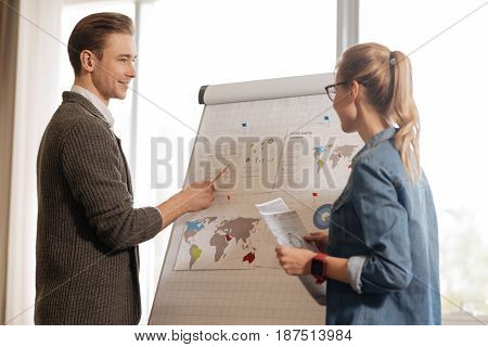 Statistical analysis. Joyful nice pleasant man standing near the flip board and pointing at it while presenting some statistical information