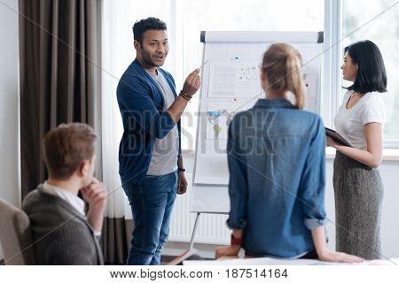 Global market analysis. Nice hard working pleasant man standing near the flip chart and presenting his report while conducting a global market analysis