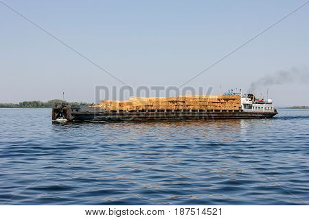 The cargo ship loaded with timber on the river Volga