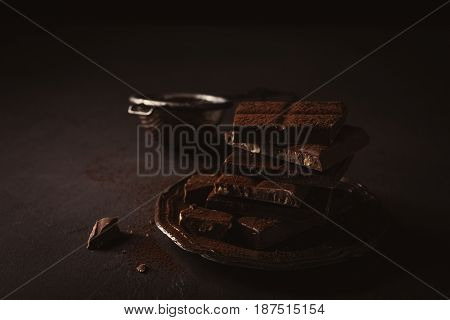 Broken chocolate pieces and cocoa powder on metal plate on brown background with copy space. Dark photo.