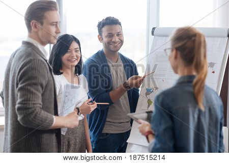 Global market trends. Joyful happy positive man standing near the flip chart and smiling while discussing global market trends while his colleagues