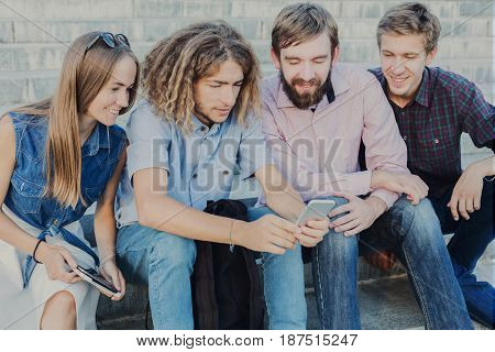 Group of young people using smartphone outdoors in urban background. Company of friends chatting or looking some funny video on gadget. Modern lifestyle concept