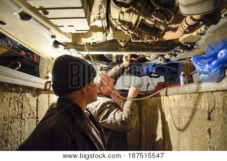 Oil Change In The Automatic Box Of The Car Volkswagen Tuareg. Car Maintenance Station.