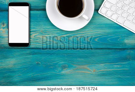 Office desk with copy space. Digital devices wireless keyboard mouse and tablet computer with empty screen on blue wooden table with cup of coffee top view