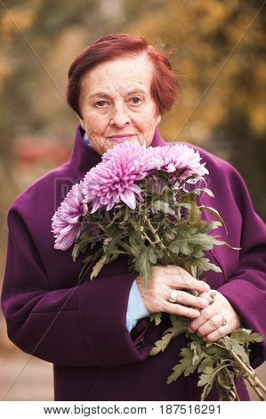 Portrait of senior woman holding flowers outdoors. Looking at camera. 80s.