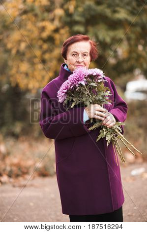 Smiling senior woman 70-75 year old holding flowers outdoors. Wearing winter jacket. Looking at camera.