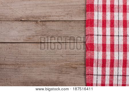 Red checkered tablecloth on an old wooden table with copy space for your text. Top view.