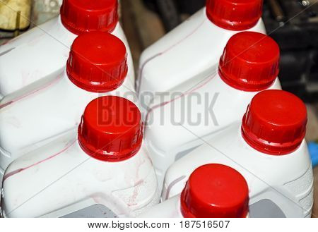 White Plastic Cans With Red Lids. Cans Of Transmission Oil