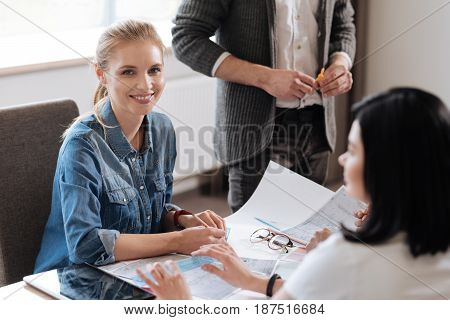 Wonderful mood. Cheerful positive nice woman sitting at the table and smiling while feeling happy about her job