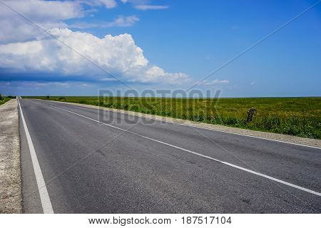 A long highway with no cars on the overgrown grass of the steppe under a blue cloudy sky