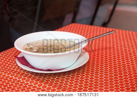 chicken soup in a white plate on a red cloth on a little table in cafe