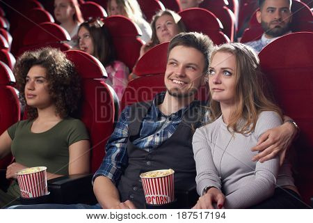 Boyfriend embracing his pretty girlfriend at cinema, when watching movie and spending time together. Couple leaning each other, sitting in modern cinema hall, holding popcorn and looking at projector.