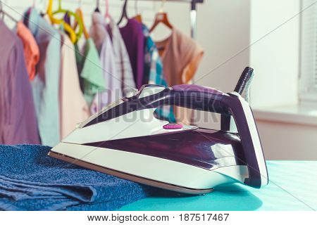 Iron on ironing board on light home interior background