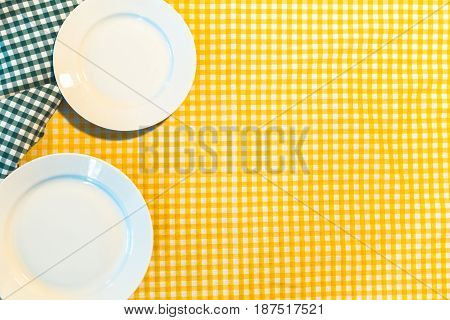 the plate on yellow checkered table cloth