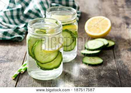 Detox water with cucumber and lemon on wooden table