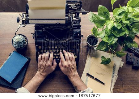 Hands typing on classic vintage typewriter