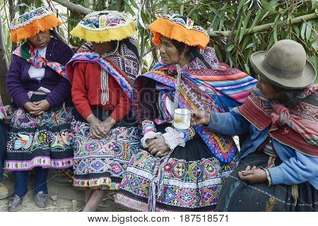 Indigenous women wearing handwoven skirts and ponchos attending local wedding ceremony. October 22 2012 -  Amaru,Peru