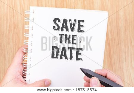 Save The Date Word On White Ring Binder Notebook With Hand Holding Pencil On Wood Table,business Con
