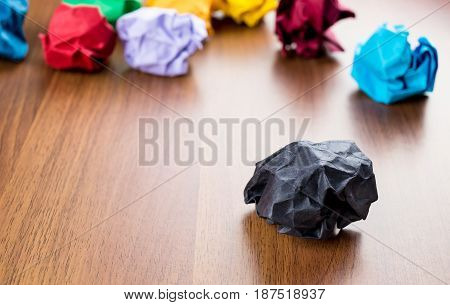 Black Crumpled Paper Ball On Dark Brown Wood Table With Group Of Colorful Crumpled Paper Ball At Bac
