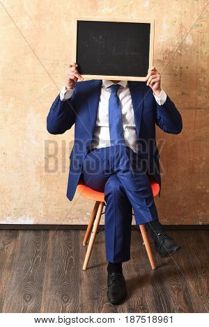 promotion. businessman in blue suit holding a blackboard