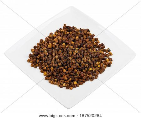 Pile of bee bread in a plate isolated on white background
