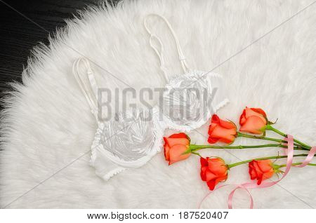 White Lace Bra On White Fur And A Bouquet Of Orange Roses. Fashionable Concept. Top View