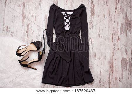 Black Dress With Long Sleeves And A Binder, Black Shoes. Wooden Background, Fashionable Concept