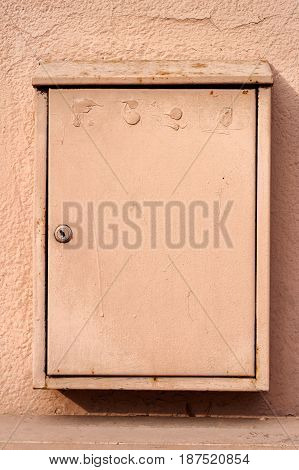 Closeup of metal mailbox hanging on beige cement wall with keyhole