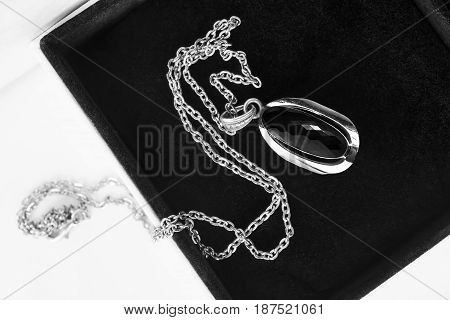 Black obsidian medallion on silver chain in jewel box closeup