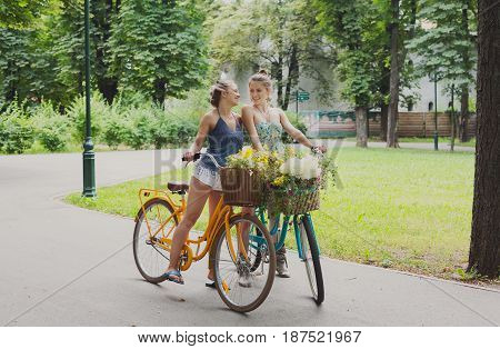 Happy boho girls gather wild flowers on bicycle ride. Beautiful female friends, youth and happiness, active summer leisure in park concept.
