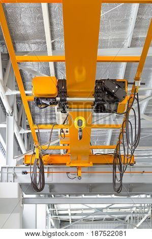 Overhead crane and hook inside factory building for lifting work.