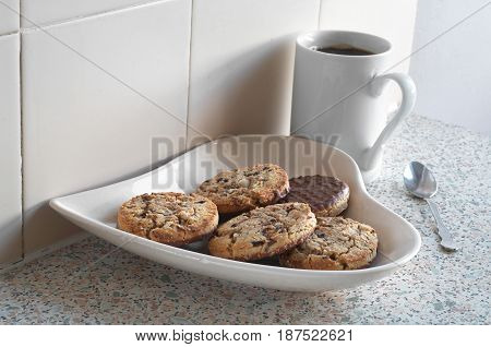 Plate in the shape of heart with chocolate cookies and black coffee on kitchen table